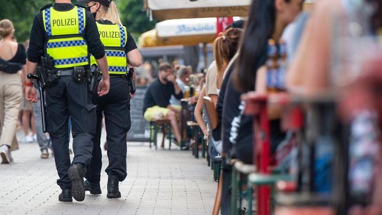 Polizisten laufen im Hamburger Schanzenviertel Streife neben Außentischen der Gastronomie. Foto: Jonas Walzberg/dpa/Archivbild