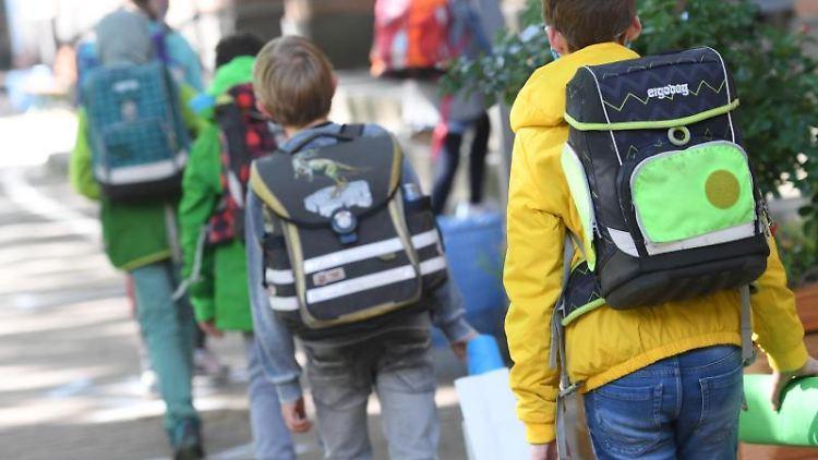 Schülerinnen und Schüler gehen ins Schulgebäude. Foto: Arne Dedert/dpa