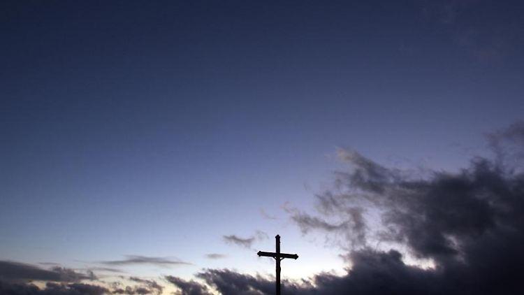 Wolken ziehen hinter einem Wegkreuz über das Voralpenland. Foto: picture alliance / dpa