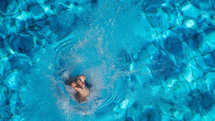 Eine Frau taucht in ein Schwimmbecken ein. Foto: Sebastian Gollnow/dpa/Archivbild