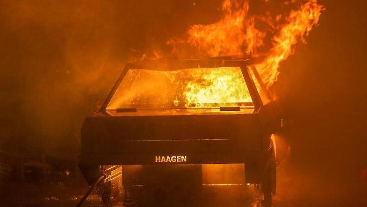 Ein brennendes Fahrzeug steht auf einer Straße. Foto: David Young/dpa/Symbolbild