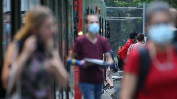 Fahrgäste verlassen einen Bahnsteig neben einer Straßenbahn. Foto: Oliver Berg/dpa/Symbolbild