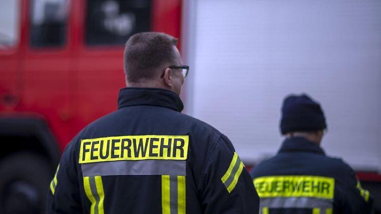 Feuerwehrmänner stehen vor einem Feuerwehrauto. Foto: Jens Büttner/zb/dpa/Illustration