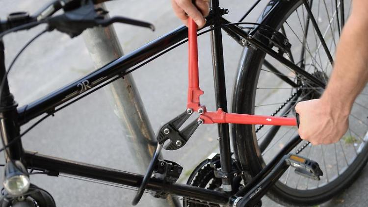 Ein Mann versucht mit einem Bolzenschneider ein Fahrradschloss aufzubrechen (gestellte Szene). Foto: Andreas Gebert/dpa/Illustration