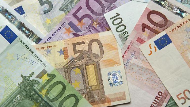 Zahlreiche Euro-Banknoten liegen auf einem Tisch. Foto: Daniel Reinhardt/dpa/Symbolbild