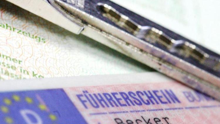 Ein Führerschein und ein Autoschlüssel liegen auf einem Fahrzeugschein. Foto: Marius Becker/dpa/Symbolbild
