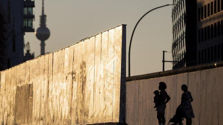 Eine Familie schaut sich an der East Side Gallery ein Stück der Berliner Mauer an. Foto: Christoph Soeder/dpa/Archivbild