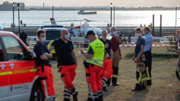 Einsatzkräfte der Feuerwehr und ein Helikopter am Willkommhöft an der Elbe. Foto: Jonas Walzberg/dpa