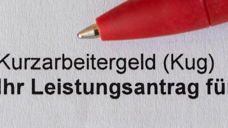 Ein roter Stift liegt auf einem Antrag für Kurzarbeitergeld. Foto: Robert Michael/dpa-Zentralbild/dpa/Symbolbild