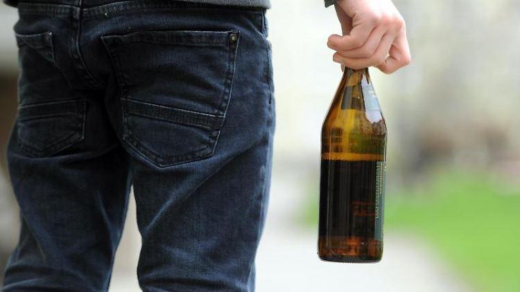 Ein Jugendlicher hält eine geöffnete Bierflasche in der Hand. Foto: Tobias Hase/dpa/Symbolbild