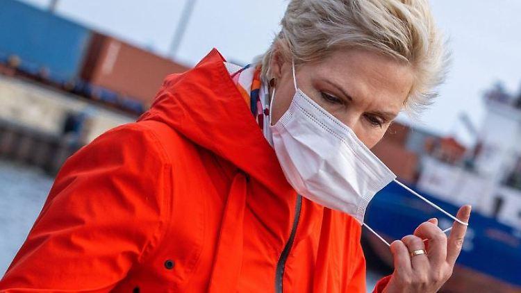 Manuela Schwesig (SPD) nimmt bei einem Termin ihre Maske ab. Foto: Jens Büttner/dpa-Zentralbild/dpa