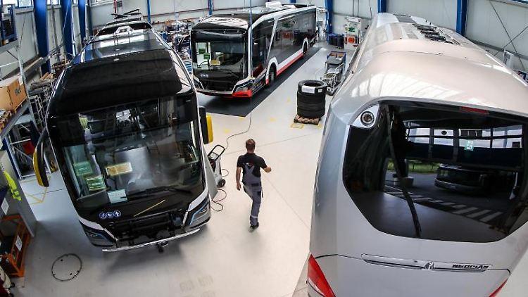 Ein Mitarbeiter geht durch eine Halle mit Elektrobussen von MAN. Foto: Jan Woitas/dpa-Zentralbild/dpa/Symbolbild