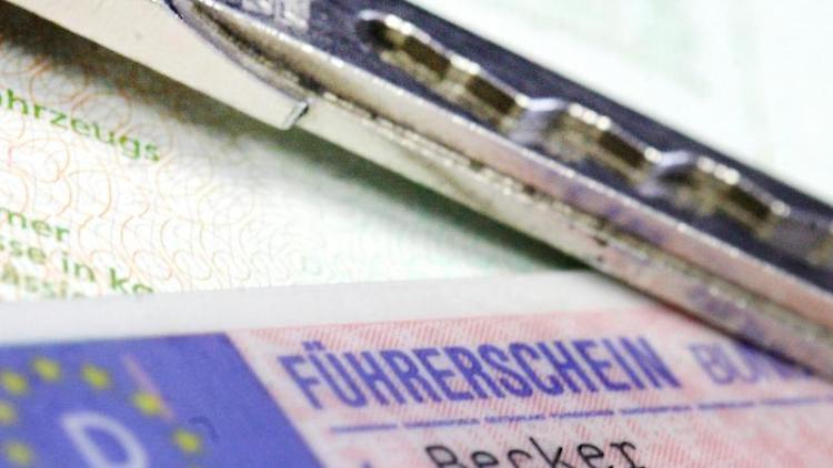 Ein Führerschein und ein Autoschlüssel auf einem Fahrzeugschein. Foto: Marius Becker/dpa/Symbolbild