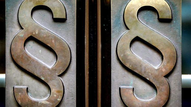 Paragrafen-Symbole sind an Türgriffen am Eingang zu einem Gericht zu sehen. Foto: Oliver Berg/dpa/Illustration