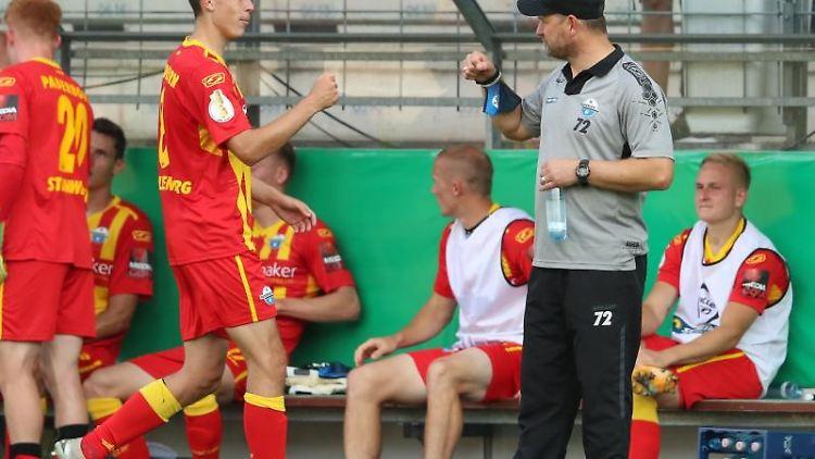 Paderborns Ron Schallenberg (l) feiert den Sieg in der 1. Runde des DFB-Pokals mit seinem Trainer Steffen Baumgart (r) . Foto: Friso Gentsch/dpa/Archivbild