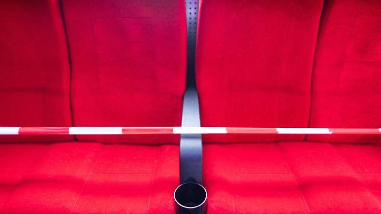 Sitze in einem Kino sind mit Absperrband versehen. Foto: Robert Michael/dpa-Zentralbild/dpa/Symbolbild