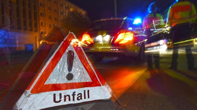 Ein Polizeifahrzeug steht mit Blaulicht auf der Straße. Daneben steht ein Warndreieck mit dem Schriftzug
