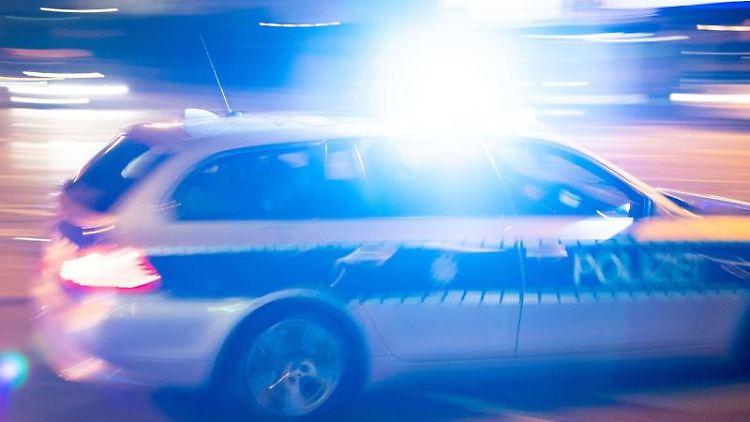 Ein Polizeiauto fährt unter Einsatz von Blaulicht und Sirene eine Straße entlang. Foto: Lino Mirgeler/dpa/Symbol