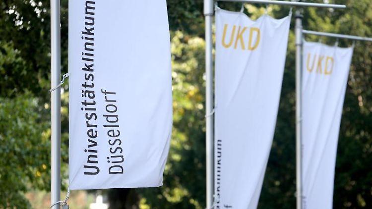 Neben dem Haupteingang zum Universitätsklinikum Düsseldorf wehen Fahnen der Klinik. Foto: Roland Weihrauch/dpa/Aktuell
