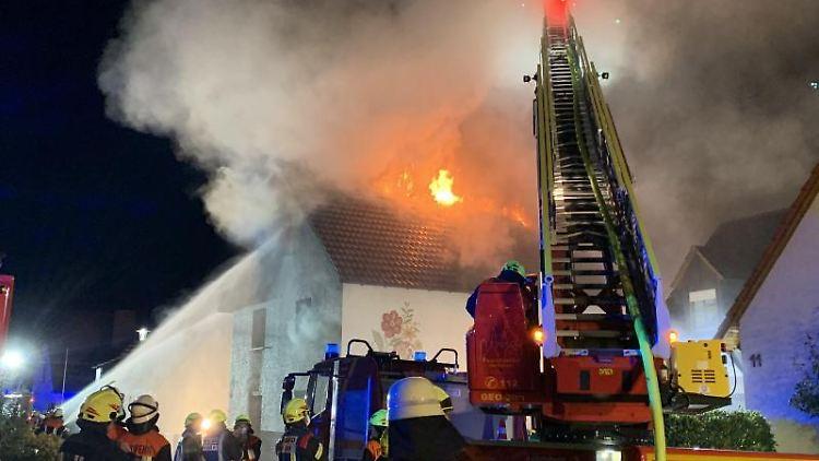 Feuerwehrleute stehen mit einer Drehleiter vor einem Haus und löschen einen Brand. Foto: Pascal Höfig/NEWS5/dpa