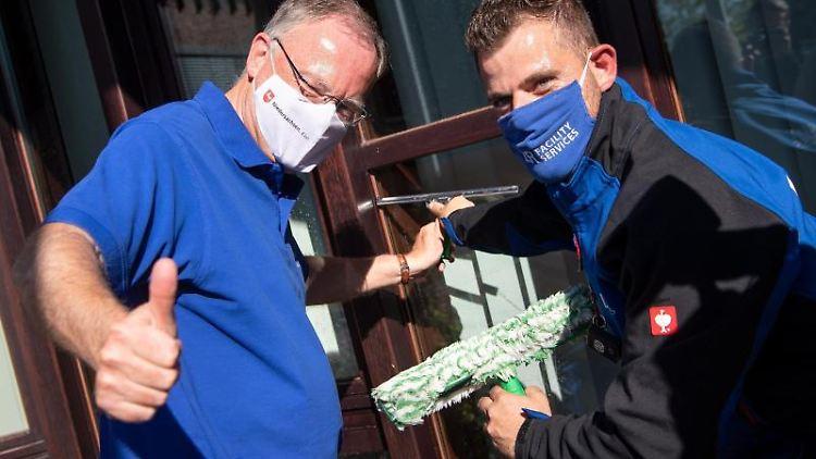 Stephan Weil (SPD, l), Ministerpräsident von Niedersachsen, und LR Facility Services, reinigen Fensterscheiben. Foto: Sina Schuldt/dpa