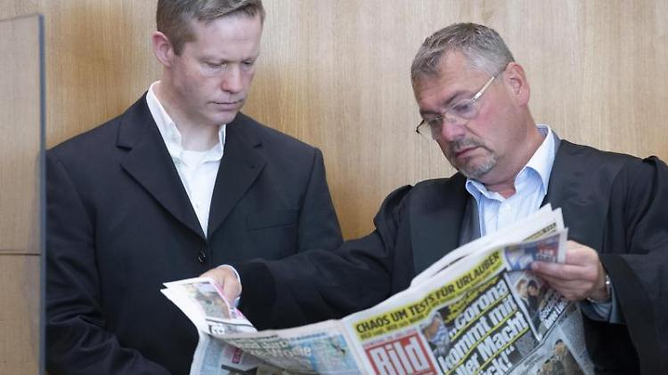 Stephan Ernst (l) mit seinem damaligen Verteidiger Frank Hannig, der in der Bild-Zeitung blättert. Foto: Boris Roessler/dpa/Archivbild