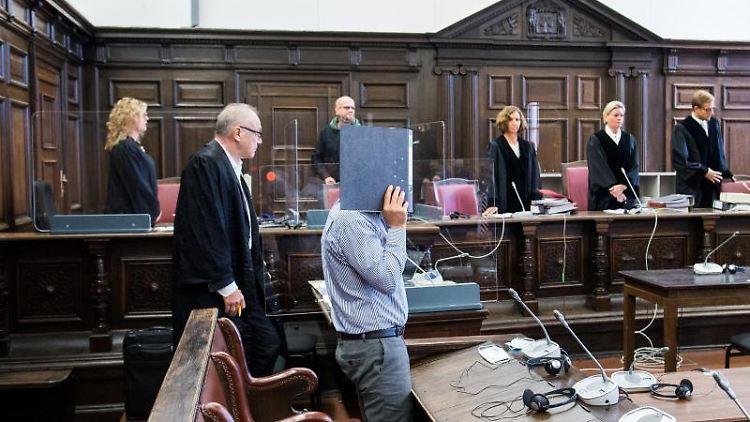 Ein 54 Jahre alter Angeklagter (vorne) steht im Landgericht im Sitzungssaal. Foto: Daniel Bockwoldt/dpa Pool/dpa