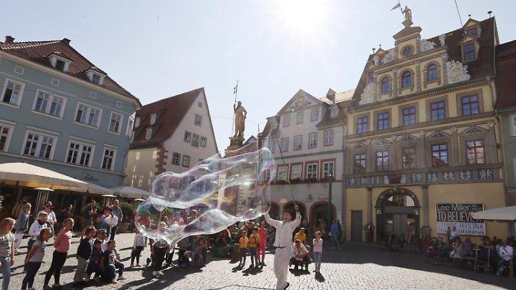 Ein Straßenkünstler erzeugt bei strahlendem Sonnenschein Seifenblasen auf dem Fischmarkt. Foto: Bodo Schackow/dpa-Zentralbild/dpa