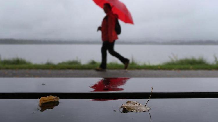Ein Spaziergänger geht im Regen eine Uferpromenade entlang. Foto: Karl-Josef Hildenbrand/dpa/Symbolbild