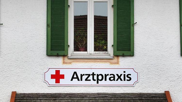 Ein Schild an einem Haus weist in einer kleinen Gemeinde auf eine Arztpraxis hin. Foto: Karl-Josef Hildenbrand/dpa/Archivbild