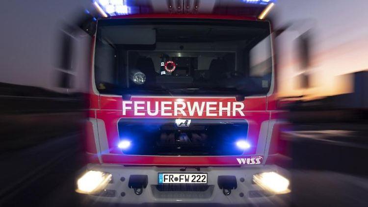 Ein Feuerwehrfahrzeug steht mit eingeschaltetem Blaulicht auf einer Straße. Foto: Patrick Seeger/dpa