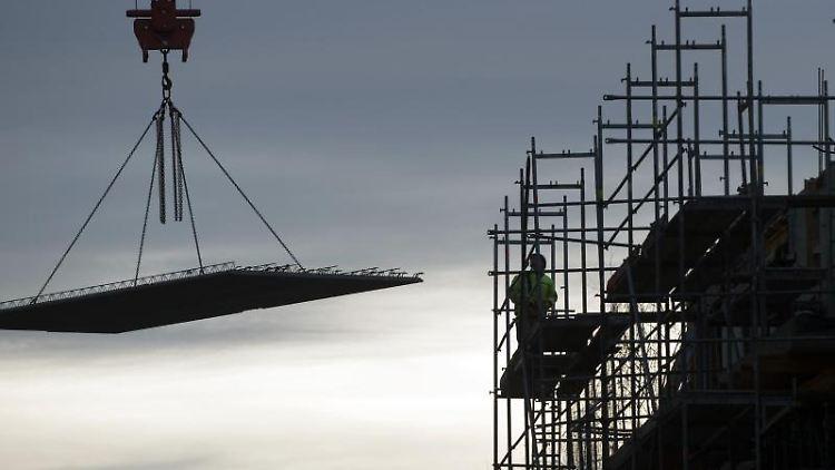 Arbeiter errichten ein Wohnhaus mit Hilfe eines Kranes. Foto: Klaus-Dietmar Gabbert/zb/dpa/Symbolbild