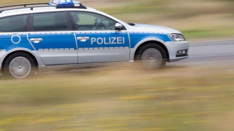 Ein Polizeifahrzeug fährt mit Blaulicht auf der Landstraße. Foto: Friso Gentsch/dpa/Symbolbild