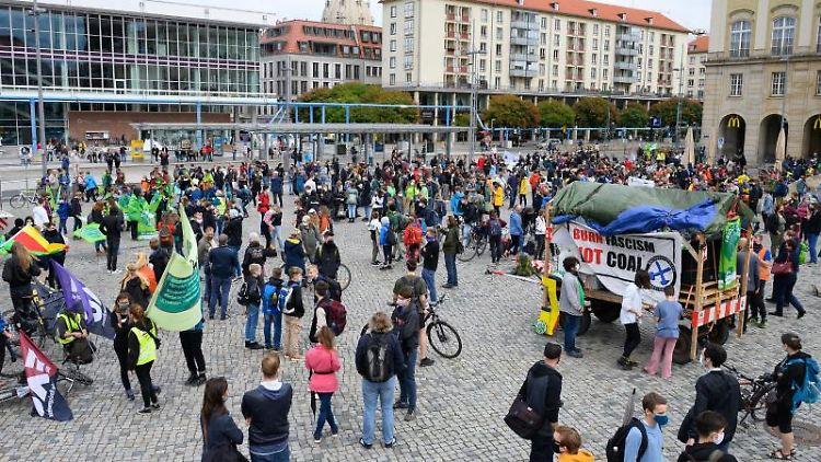 Teilnehmer einer Aktion der Klimabewegung Fridays For Future stehen auf dem Altmarkt. Foto: Sebastian Kahnert/dpa-Zentralbild/dpa