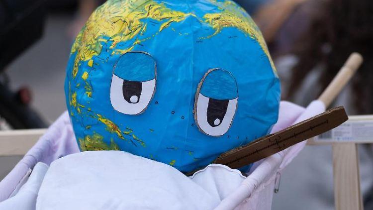 Eine Weltkugel mit Thermometer ist während des globalen Klimastreiks der Klimaschutzbewegung Fridays for Future aufgebaut. Foto: Peter Steffen/dpa/Aktuell