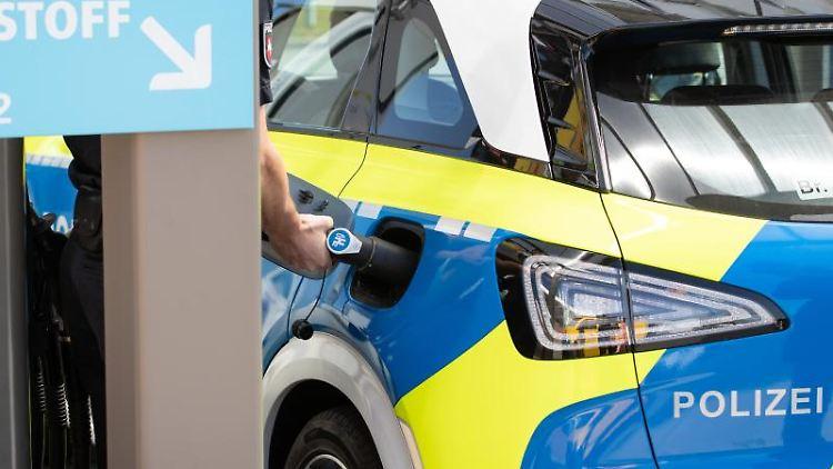 """Ein Polizist betankt einen Streifenwagen der Marke Hyundai, Modell """"Nexo"""