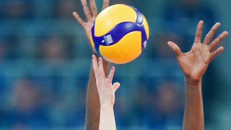Händen greifen in einem Spiel nach einem Volleyball. Foto: Uwe Anspach/dpa/Symbolbild