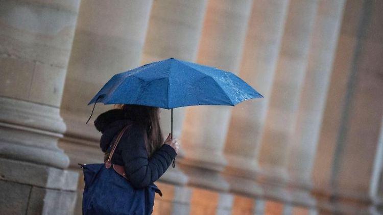 Eine Passantin geht bei Regen durch die Stadt. Foto: Marijan Murat/dpa/Symbolbild