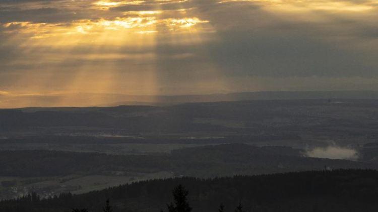 Die Sonne geht hinter einem dichten Wolkenband über den Ausläufern des Taunus unter. Foto: Boris Roessler/dpa/Archivbild
