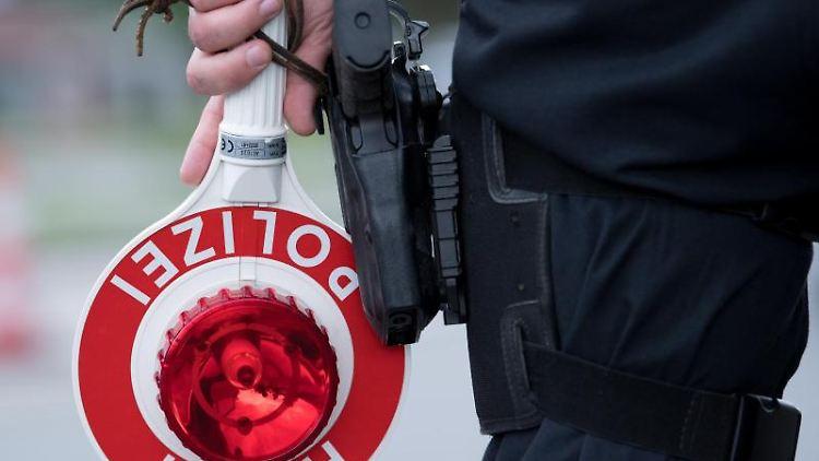 Ein Polizist hält eine Kelle mit der Aufschrift