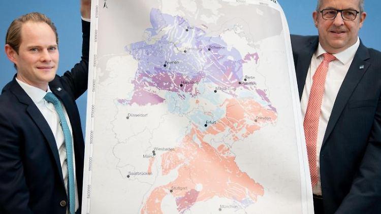 Stefan Studt (r) und Steffen Kanitzvon der BGE zeigen eine Karte mit Gebieten für die Endlagersuche. Foto: Kay Nietfeld/dpa