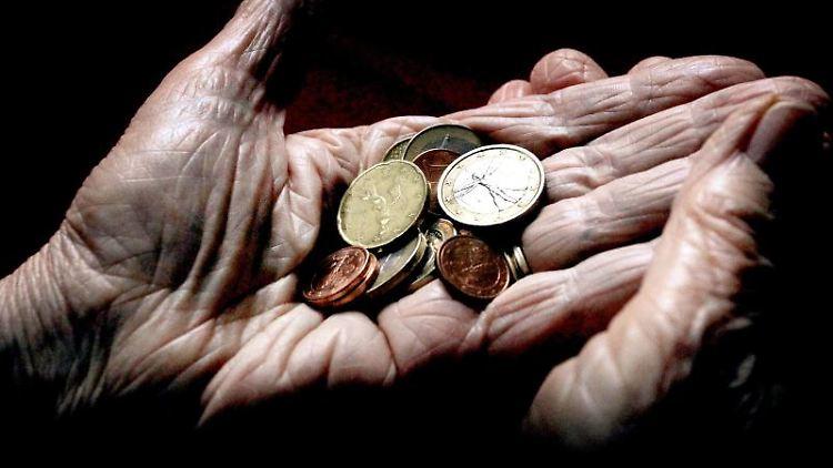 Eine 83-jährige Frau hält verschiedene Euromünzen. Foto: Karl-Josef Hildenbrand/dpa/Archivbild