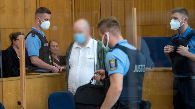 Der des Mordes an dem Politiker Walter Lübcke Mitangeklagte Markus H. (M) betritt mit Mund-Nasen-Schutz den Gerichtssaal. Foto: Thomas Lohnes/Getty Images Europe/Pool/dpa/Archivbild