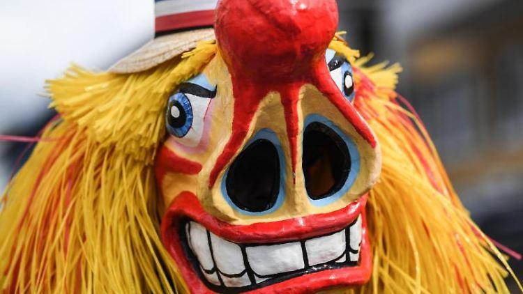 Ein Narr mit einer Masken nimmt an einem Umzug teil. Foto: Patrick Seeger/dpa/Symbolbild
