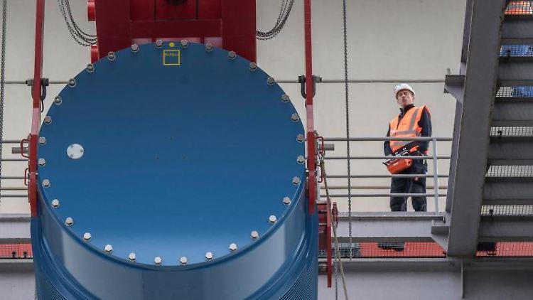Ein Castorbehälter wird in das Innere eines der Reaktorblöcke des AKW Biblis gehoben. Foto: Boris Roessler/dpa/Symbolbild