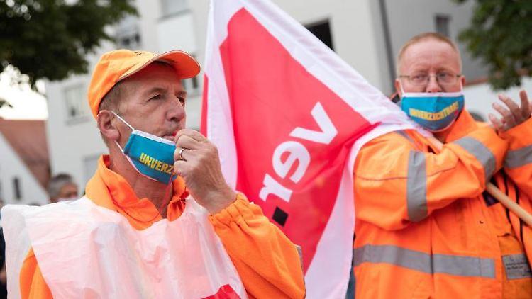 Demonstranten der Entsorgungsbetriebe halten bei einem Protest eine Verdi-Fahne in der Hand. Foto: Tom Weller/dpa/Symbolbild