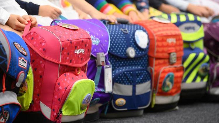 Schüler haben ihre Schulranzen vor sich abgestellt. Foto: Robert Michael/dpa-Zentralbild/dpa/Archiv