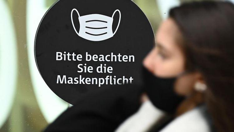 Eine Frau, die einen Mund-Nasen-Schutz trägt, an einem Hinweis mit der Aufschrift