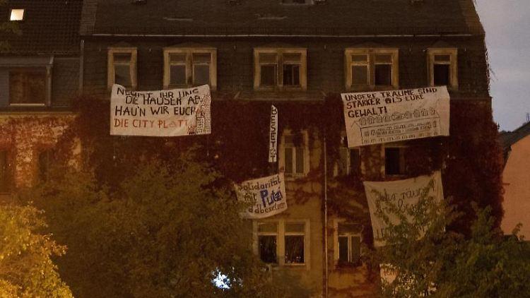 Transparente der Aktivisten hängen an den Fenstern des leerstehenden Wohnhauses in Dresden. Foto: Sebastian Kahnert/dpa-Zentralbild/dpa