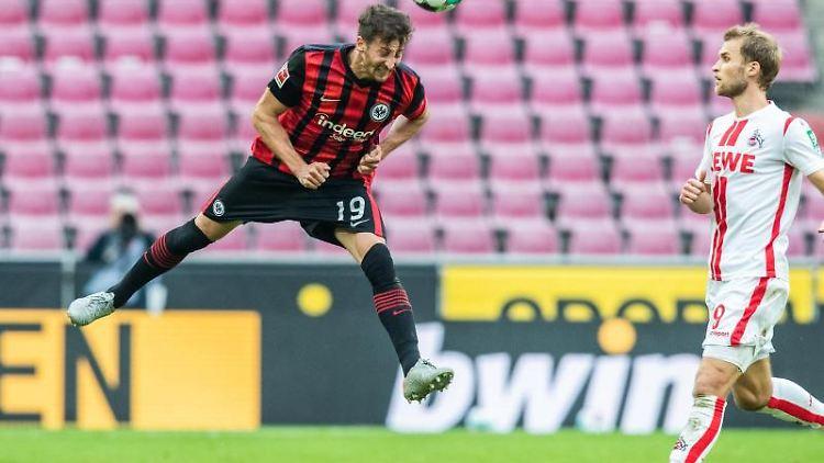 Frankfurts David Abraham (l) köpft den Ball während Kölns Sebastian Andersson (r) versucht zu verteidigen. Foto: Marcel Kusch/dpa